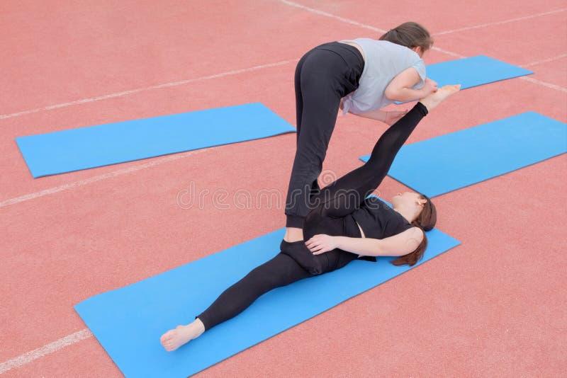 Dos muchachas hacen un etude gimn?stico Ejercicio en un par de estirar los m?sculos de las piernas Los estudiantes juegan deporte imagenes de archivo