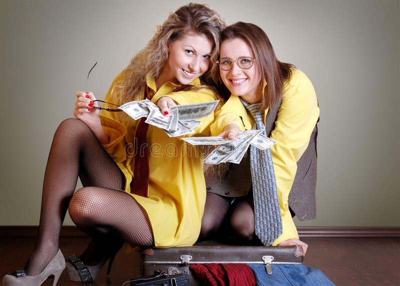 Dos muchachas hermosas con el dinero foto de archivo libre de regalías