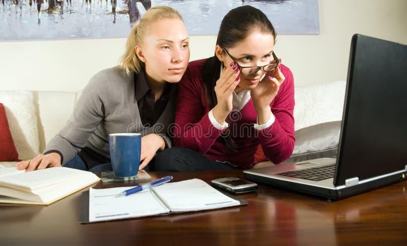 Dos muchachas hermosas con la computadora portátil en la oficina fotografía de archivo