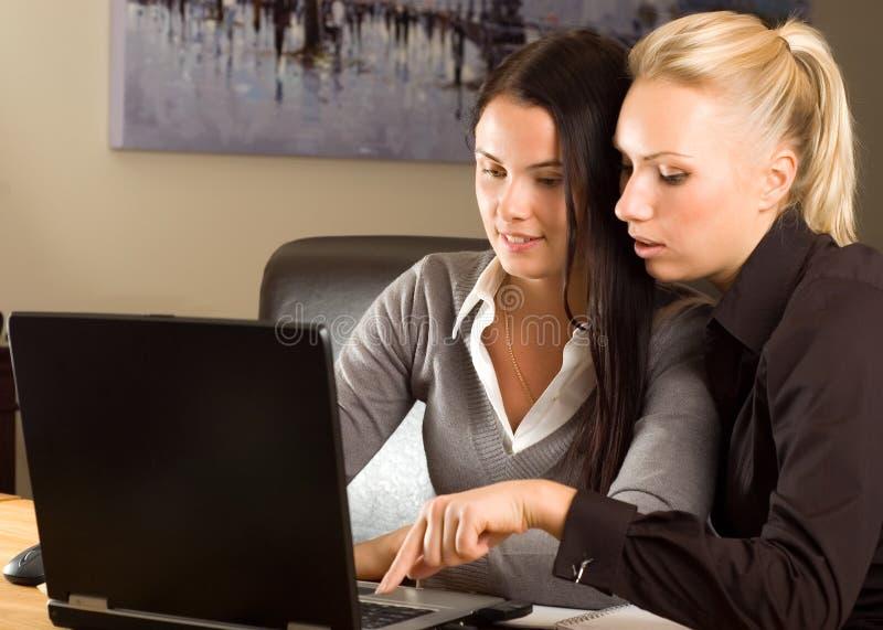 Dos muchachas hermosas con la computadora portátil en la oficina imagen de archivo libre de regalías