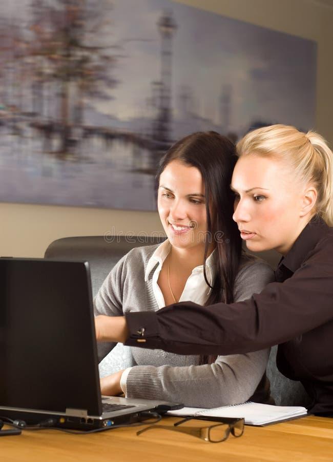 Dos muchachas hermosas con la computadora portátil en la oficina imagen de archivo