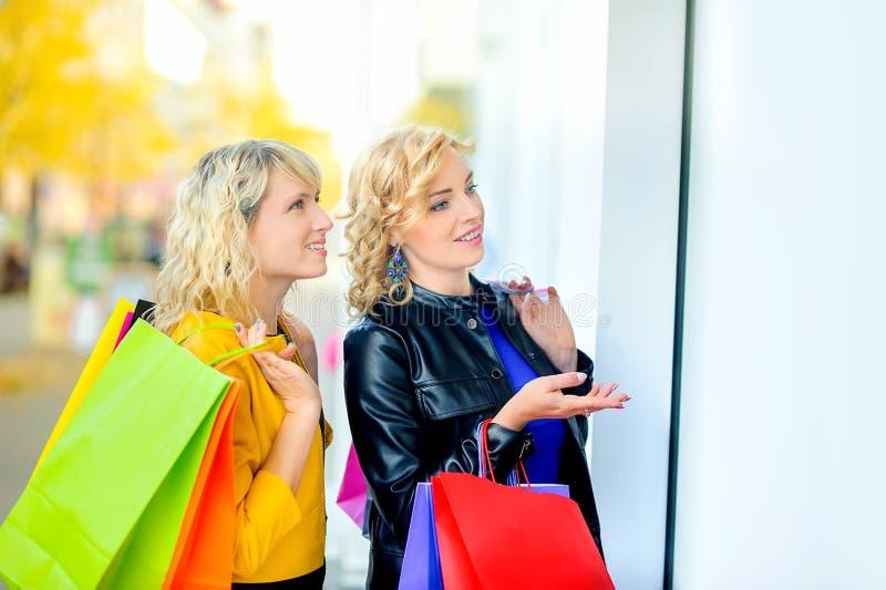 Dos muchachas hermosas con los bolsos de compras están mirando la ventana y la sonrisa de la tienda fotografía de archivo libre de regalías