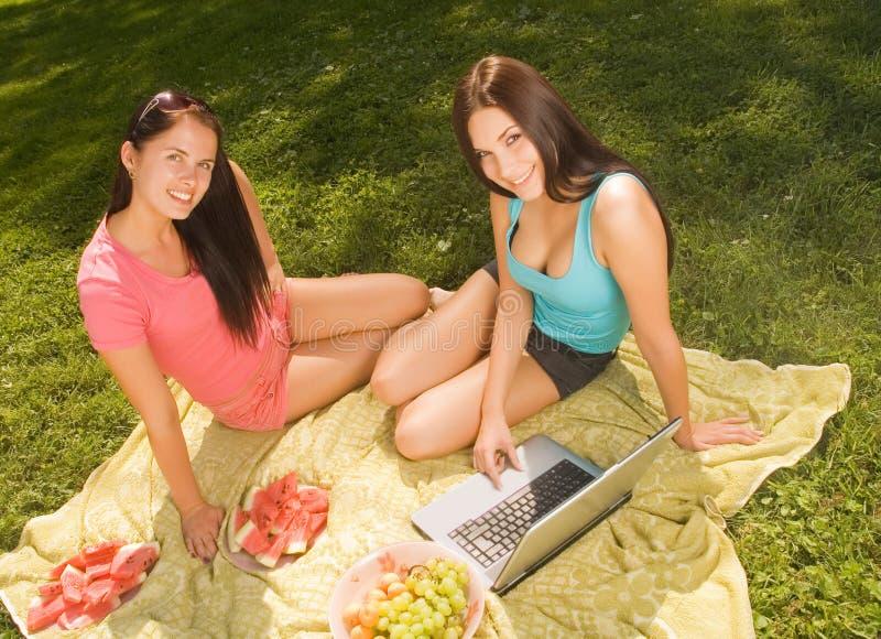 Dos muchachas hermosas del estudiante al aire libre imagen de archivo libre de regalías