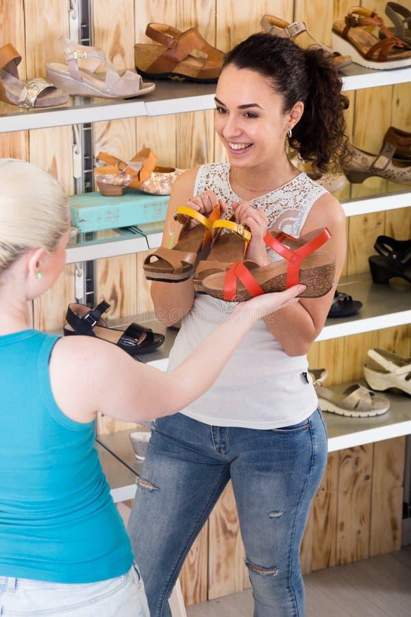 Dos muchachas hermosas eligen los zapatos en la tienda imagen de archivo