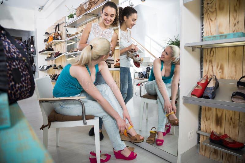 Dos muchachas hermosas eligen los zapatos en la tienda imagen de archivo libre de regalías