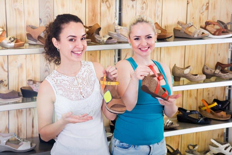 Dos muchachas hermosas eligen los zapatos en la tienda foto de archivo libre de regalías