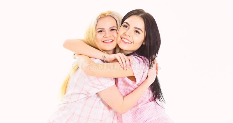 Dos muchachas hermosas en abrazos del pijama Concepto de los mejores amigos Las señoras en caras sonrientes se abrazan firmemente fotos de archivo libres de regalías