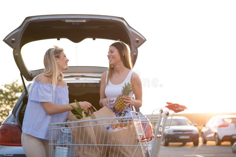 Dos muchachas hermosas en el estacionamiento delante del supermercado foto de archivo libre de regalías