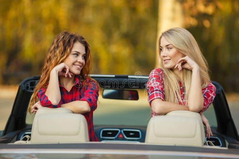 Dos muchachas hermosas están viajando en convertible imagen de archivo