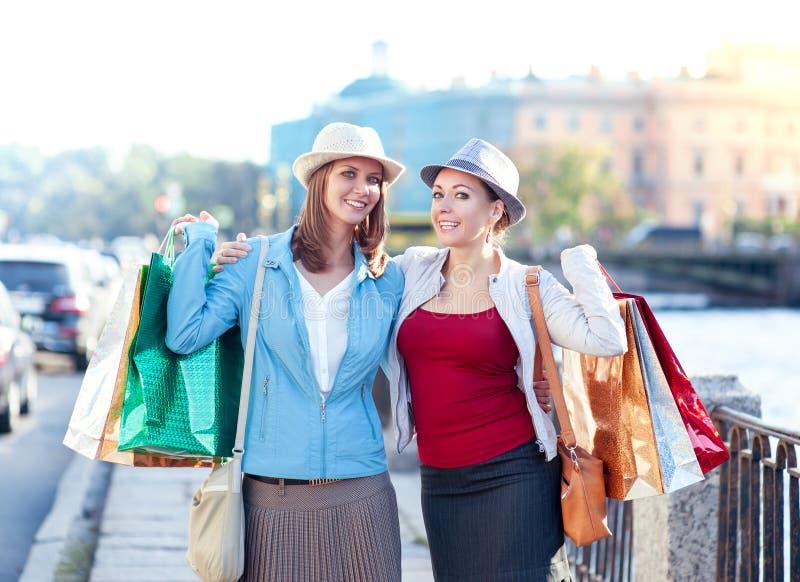 Dos muchachas hermosas felices con abrazo de los panieres en la ciudad imagen de archivo libre de regalías