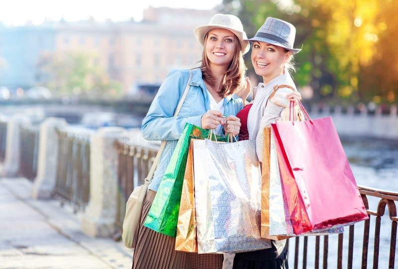 Dos muchachas hermosas felices con los panieres en la ciudad imagen de archivo libre de regalías