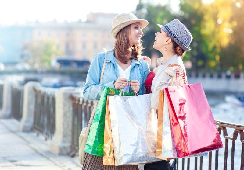Dos muchachas hermosas felices con los panieres en la ciudad imagen de archivo