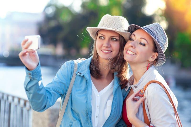 Dos muchachas hermosas felices tomadas la imagen de ellos mismos en la ciudad imagen de archivo libre de regalías
