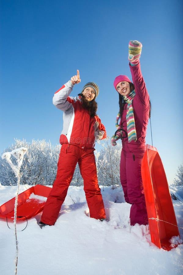 Dos muchachas hermosas jovenes con los trineos fotos de archivo libres de regalías