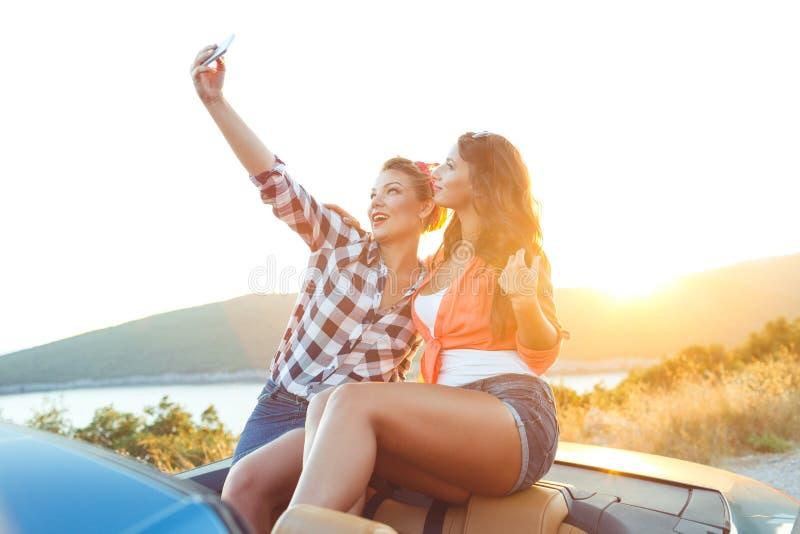 Dos muchachas hermosas jovenes están haciendo el selfie en un convertible fotos de archivo libres de regalías