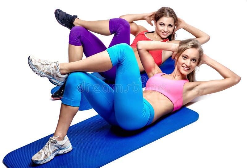 Dos muchachas que hacen ejercicio abdominal fotografía de archivo