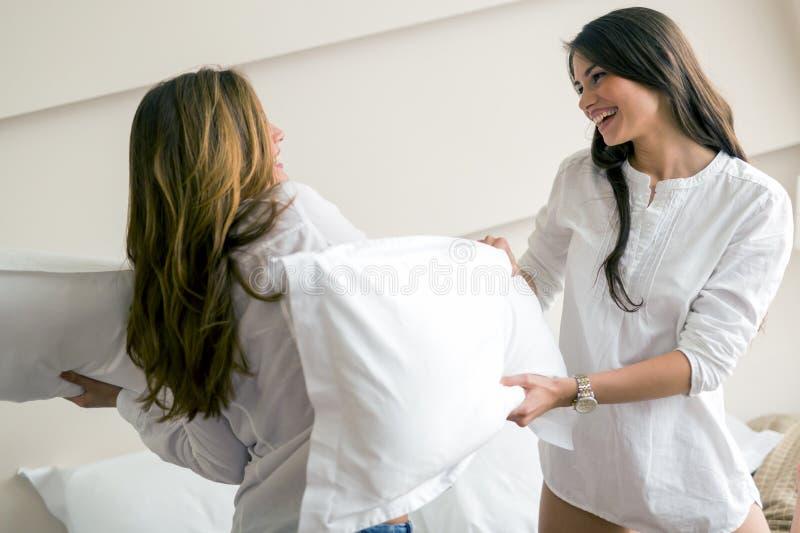 Dos muchachas hermosas que luchan con las almohadas fotos de archivo