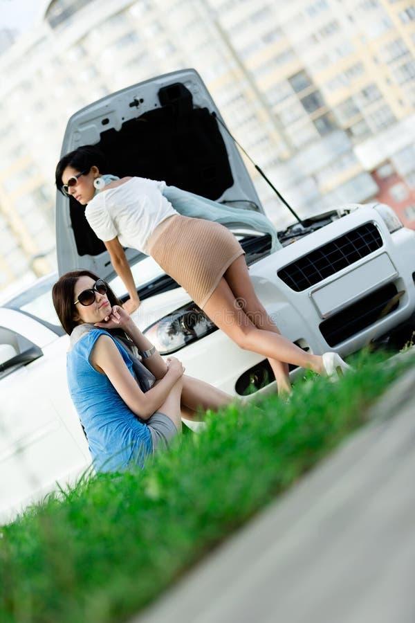 Dos muchachas intentan reparar el coche quebrado en la carretera fotografía de archivo libre de regalías