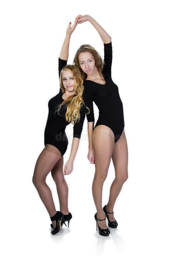 Dos muchachas jovenes de los deportes en un fondo blanco foto de archivo