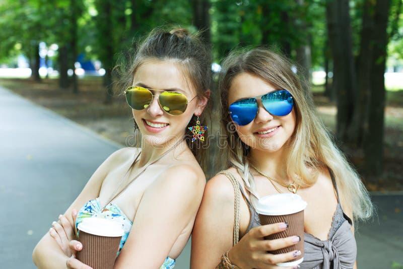 Dos muchachas jovenes hermosas del boho tienen café en parque foto de archivo