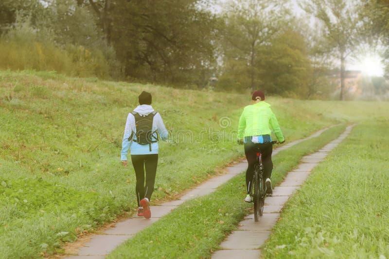 Dos muchachas juegan deportes en el tiempo de la mañana soleada Ciclo y el caminar bajo gotas de lluvia en tiempo soleado Deporte imagenes de archivo