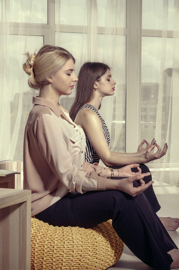 Dos muchachas meditan en la oficina después de trabajo imagen de archivo libre de regalías