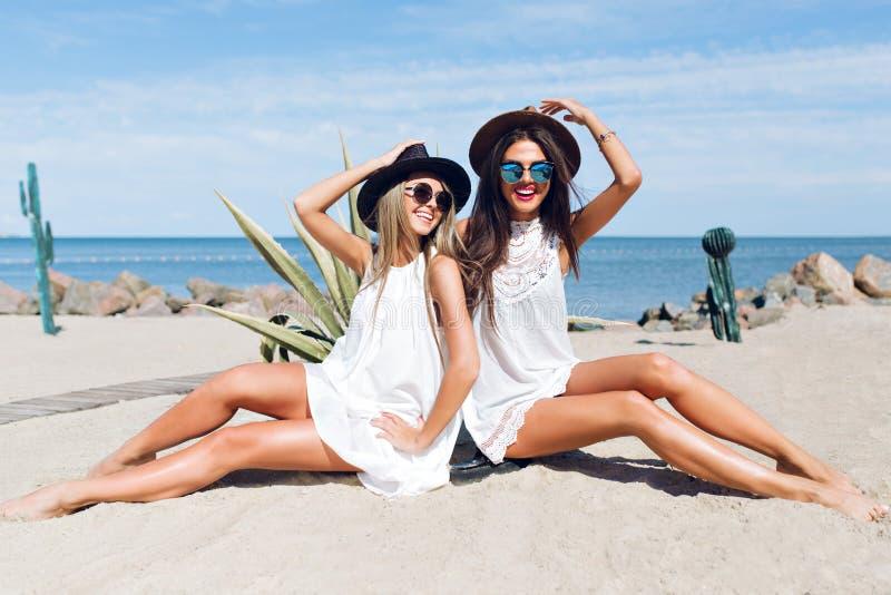 Dos muchachas morenas y rubias atractivas con el pelo largo se est?n sentando en la playa cerca del mar Llevan los sombreros, gaf fotos de archivo libres de regalías