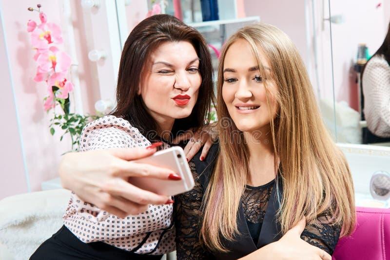 Dos muchachas morenas y un rubio hacen un selfie en un salón de belleza imágenes de archivo libres de regalías