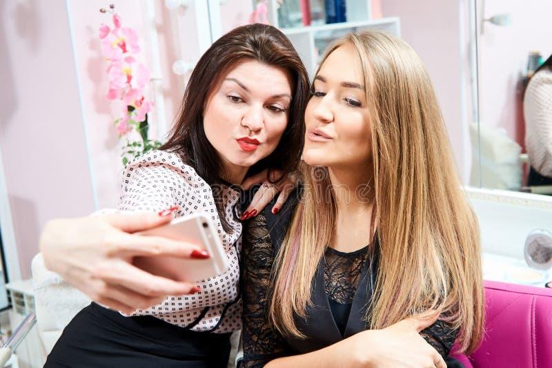 Dos muchachas morenas y un rubio hacen un selfie en un salón de belleza fotografía de archivo