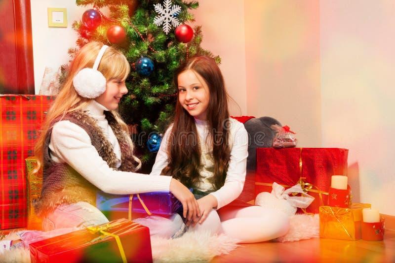 Dos muchachas preciosas bajo el árbol de navidad imagen de archivo libre de regalías