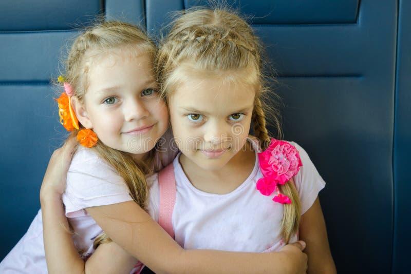 Dos muchachas que abrazan mirada en el marco, sentándose en un tren eléctrico, primer fotos de archivo