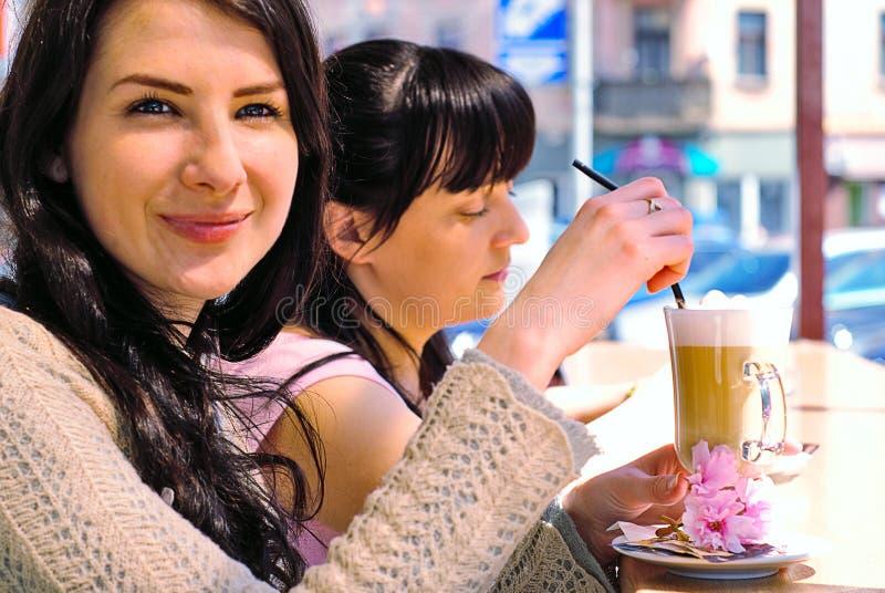Dos muchachas que beben cappuccino foto de archivo