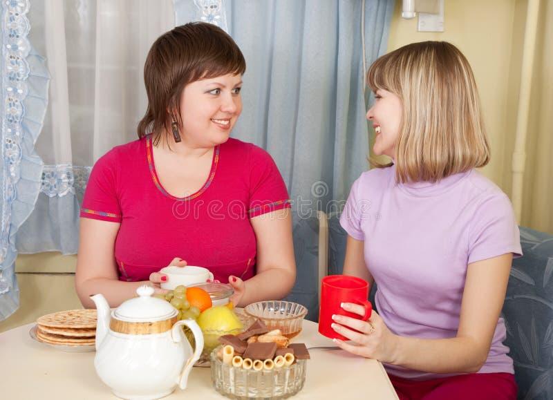 Dos muchachas que beben té y el cotilleo fotos de archivo libres de regalías