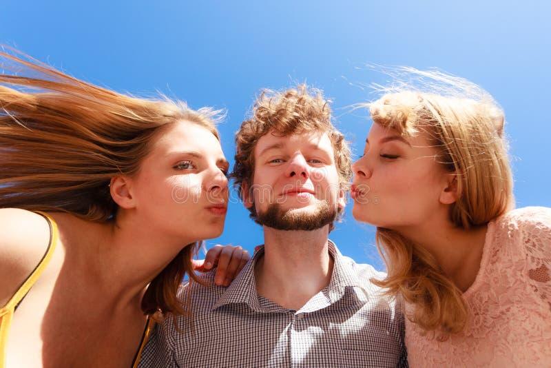 Dos muchachas que besan a un muchacho que se divierte al aire libre imágenes de archivo libres de regalías
