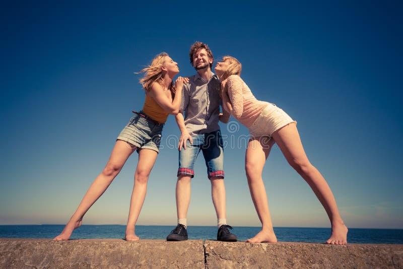 Dos muchachas que besan a un muchacho que se divierte al aire libre foto de archivo