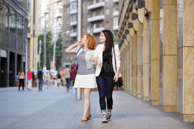 Dos muchachas que caminan en una ciudad fotografía de archivo libre de regalías