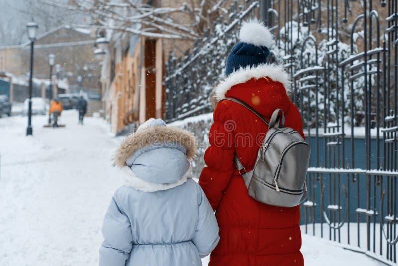 Dos muchachas que caminan a lo largo de la calle nevosa del invierno de la ciudad, niños están llevando a cabo las manos, detrás  fotos de archivo