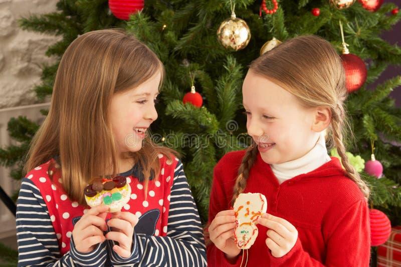 Dos muchachas que comen las galletas delante del árbol foto de archivo