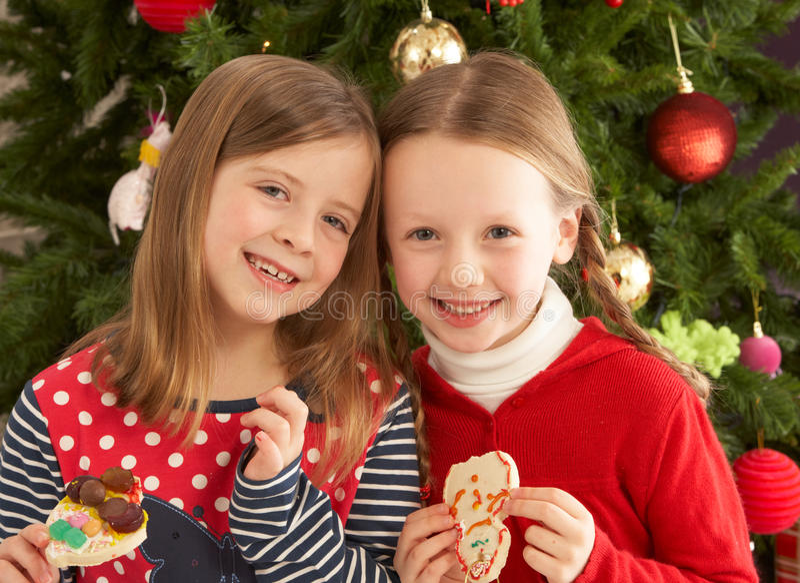 Dos muchachas que comen las galletas delante del árbol fotos de archivo libres de regalías