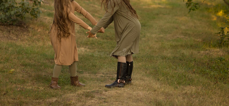Dos muchachas que corren alrededor, haciendo girar en la hierba en el parque, en el bosque Manos que suben, un paseo imagen de archivo