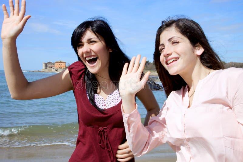Dos muchachas que dicen hola a los amigos fotos de archivo
