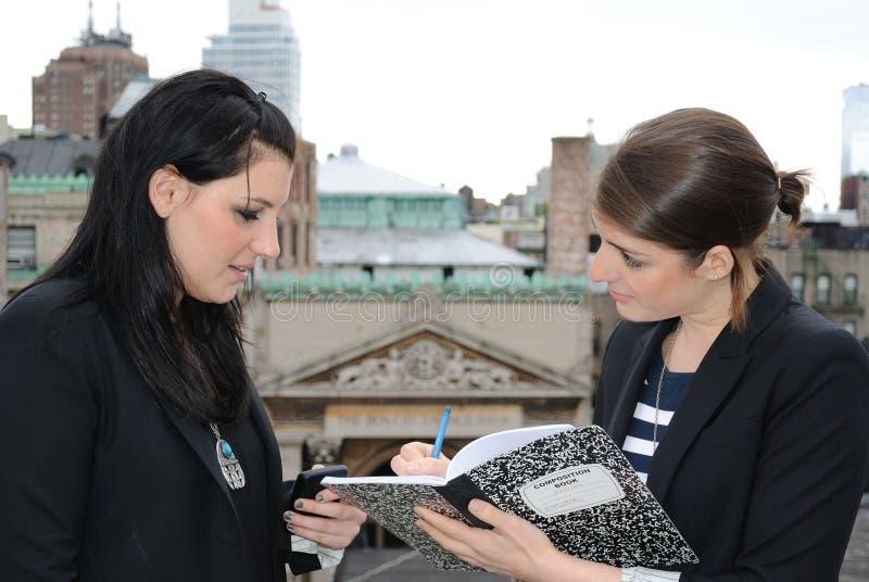 Dos muchachas que dictan notas foto de archivo