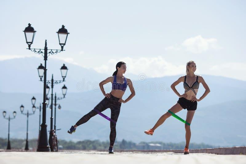 Dos muchachas que hacen deportes con las bandas de la resistencia foto de archivo