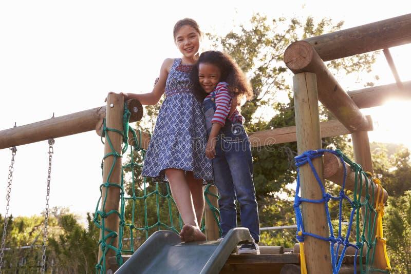 Dos muchachas que juegan al aire libre en casa en diapositiva del jardín fotografía de archivo libre de regalías