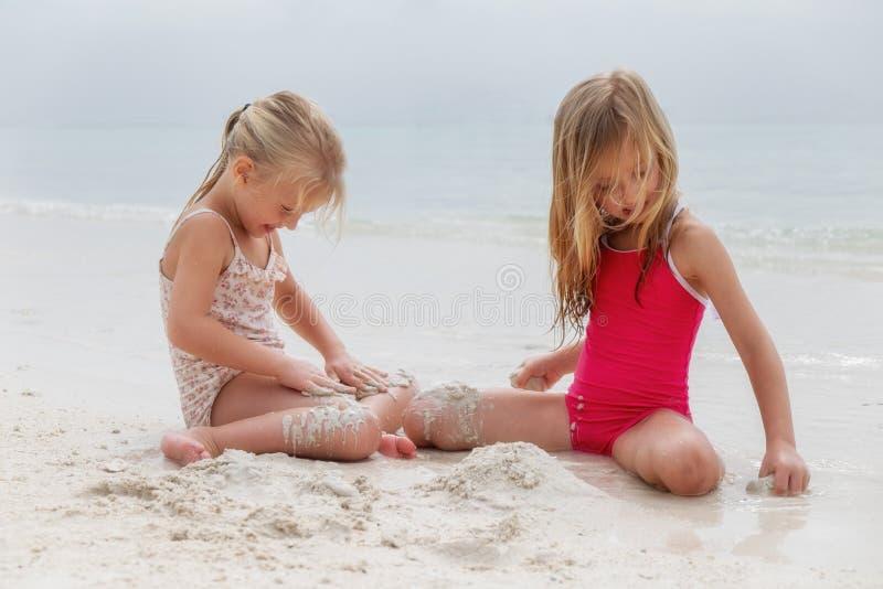 Dos muchachas que juegan en una playa imagenes de archivo