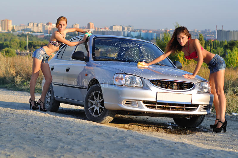 Dos muchachas que lavan el coche fotos de archivo