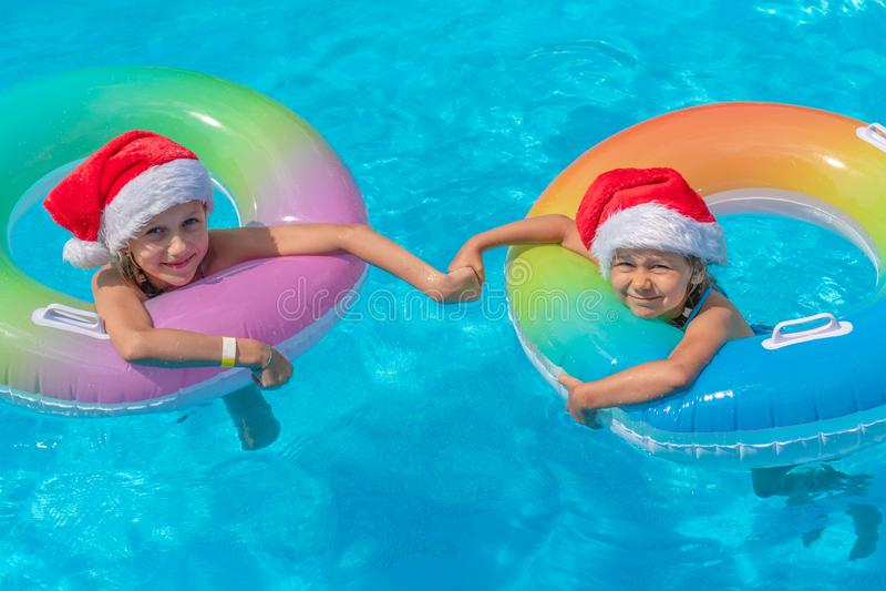 Dos muchachas que llevan los sombreros de Santa Claus están nadando en una piscina azul en un día soleado y una sonrisa brillante imagen de archivo