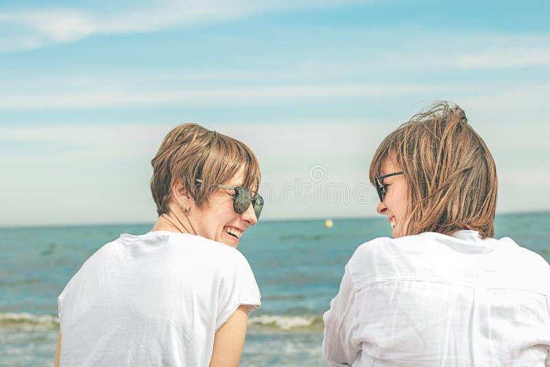 Dos muchachas que miran uno a por el mar Expresión de la amistad y de la complicidad imagenes de archivo