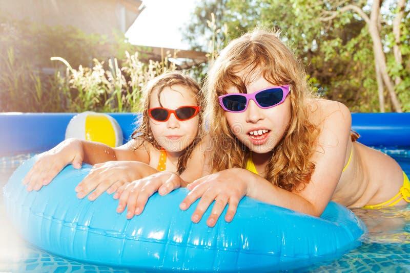 Dos muchachas que nadan en la piscina con el anillo de goma fotos de archivo