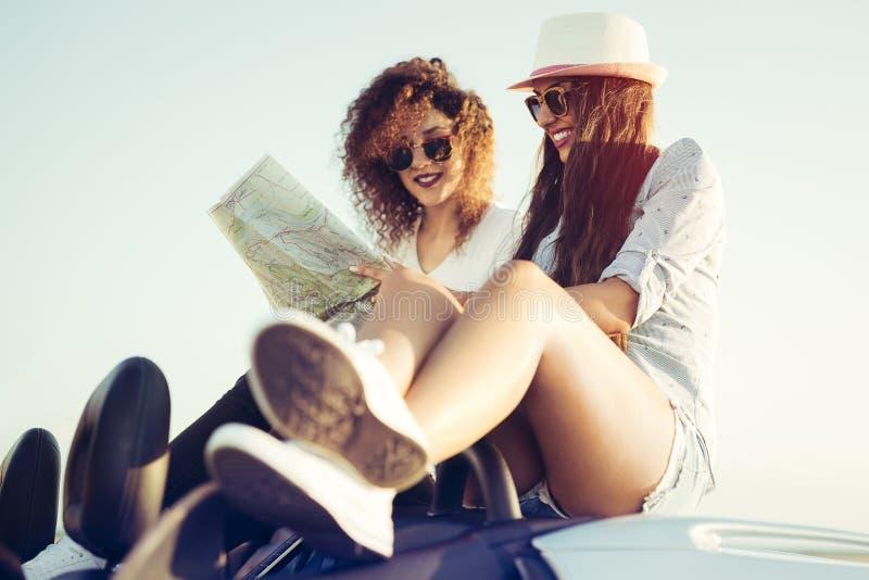 Dos muchachas que planean su viaje por carretera de la playa del verano con el convertible imagen de archivo